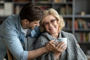 Happy middle-aged mother relax in chair drink tea enjoy family weekend reunion with grown-up son